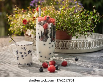 A healthy breakfast with fresh raspberries, blueberries and yogurt. Romantic porcelain cup of coffee in the sunshine on a background of plants and flowers.