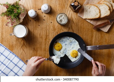 Healthy breakfast with fried eggs in a frying pan on a wooden table