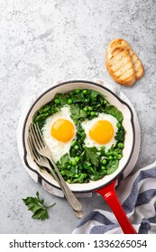 Healthy breakfast. fried eggs with kale, spinach and green peas in red skillet , top view, copy space