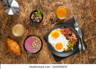 Healthy breakfast - fried eggs and smoothie bowl on a wooden background. Top view. Flat lay