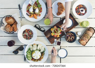 Healthy breakfast with friends, granola, yogurt, fruit salad, avocado and poached egg, croissants, bread, coffee, juice  top view