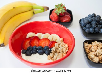 A healthy breakfast of fruit and granola on yogurt.