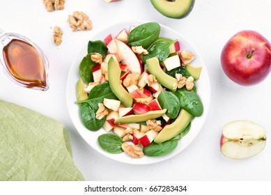 Healthy breakfast with fruit salad from apples, avocado, spinach and nuts on light background, top view