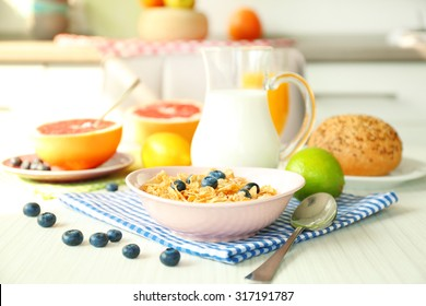 Healthy breakfast with fruits and berries on table in kitchen