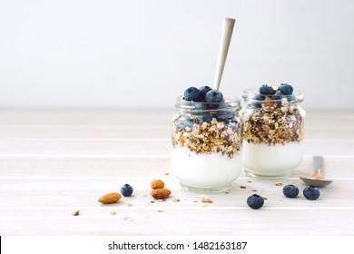 Healthy breakfast in glass jar with yogurt, muesli and blueberries.  Healthy food