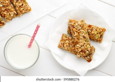 Healthy breakfast with granola bars and milk on white wooden table. Top view.