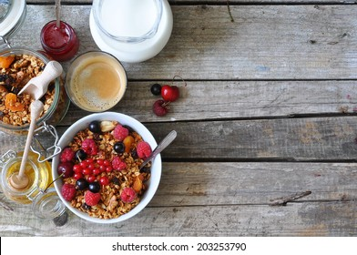 Healthy breakfast with granola, berries, milk, honey and coffee, selective focus, space for text