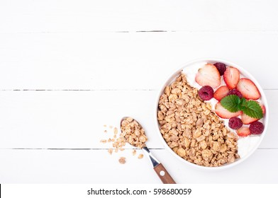 Healthy breakfast with granola, berries and yogurt on white wooden background. Healthy eating oatmeal. Top view. Copy space