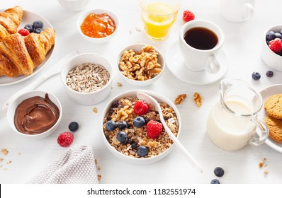 healthy breakfast with granola, berry, nuts, croissant, jam, chocolate spread and coffee