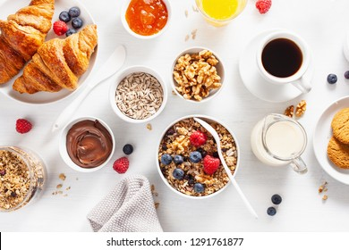 healthy breakfast with granola, berry, nuts, croissant, jam, chocolate spread and coffee. Top view