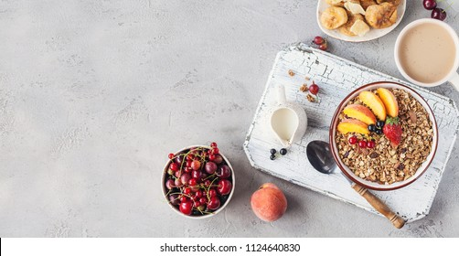Healthy breakfast with granola and dried fruit, fresh fruit. Cup of coffee with milk