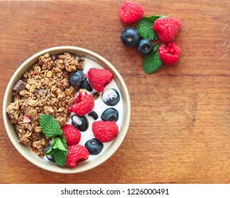 Healthy breakfast. Granola, muesli with yogurt and fresh berries in a bowl on wooden background, top view, flat lay.