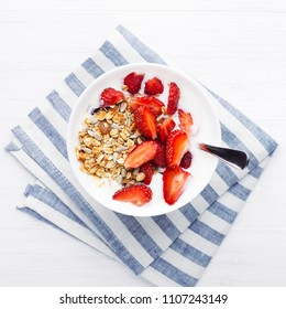 Healthy breakfast with granola, yoghurt and strawberry on the table. Top view.