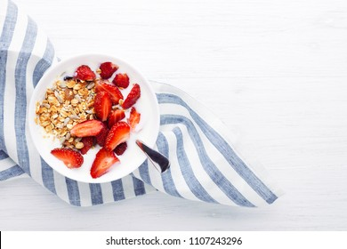 Healthy breakfast with granola, yoghurt and strawberry on the table. Top view with place for text.