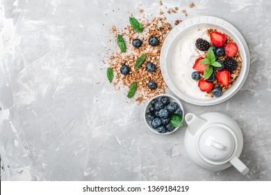 Healthy breakfast with granola, yogurt, fruits, berries on white background.
