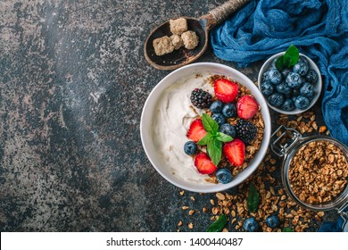 Healthy breakfast with granola, yogurt, fruits, berries on dark metal background. Summer homemade breakfast.
