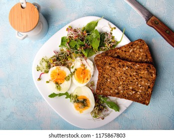 Healthy breakfast: Hard boiled eggs, fresh radish sprouts, arugula and dark whole wheat  bread with herb sauce, on blue background