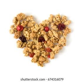 Healthy breakfast: heart-shaped crunchy muesli, isolated on white