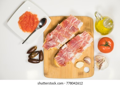 Healthy breakfast with homemade bread toast with natural tomato sauce and acorn-fed Iberian ham with extra virgin olive oil and fresh garlic