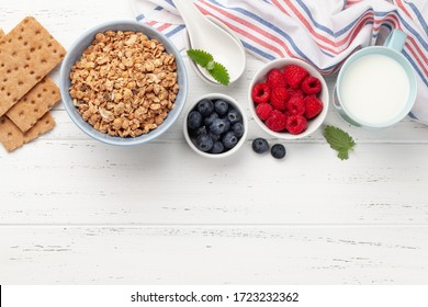 Healthy breakfast with homemade granola and fresh berries on wooden background. Top view with copy space