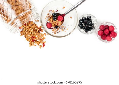 Healthy breakfast. Homemade oat granola with milk, walnuts, cashew and dried cherry in glass cup, blackcurrant and raspberry. Isolated on white background. Copy space. Top view