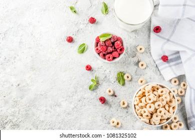 Healthy breakfast ingredients. Breakfast cereal corn rings, milk or yogurt glass, raspberries and mint on grey stone background, copy space top view