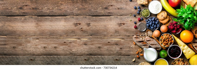 Healthy breakfast ingredients, food frame. Granola, egg, nuts, fruits, berries, toast, milk, yogurt, orange juice, cheese, banana, apple on wooden rustic background, top view, copy space. Banner