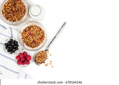 Healthy breakfast ingredients. Homemade oat granola with walnuts, cashew and dried cherry in glass cup, milk in bottle, blackcurrant and raspberry. Isolated on white background. Copy space. Top view
