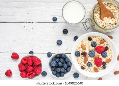 Healthy breakfast ingredients. homemade oats with raspberries and blueberries, milk and nuts on white wooden background. top view with copy space