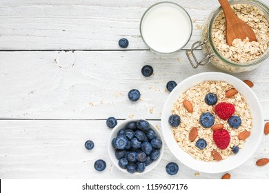 Healthy breakfast ingredients. homemade oats with raspberries and blueberries, milk and nuts for muesli on white wooden background. top view with copy space