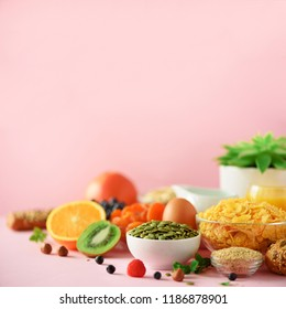 Healthy breakfast ingredients. Square crop. Oat and corn flakes, eggs, nuts, fruits, berries, toast, milk, yogurt, orange, banana, peach on pink background. Copy space.