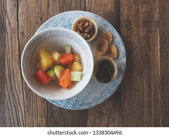 Healthy breakfast, juicy salad with dried fruits on a rustic wooden table, vegetarian food or healthy eating concept