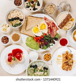 Healthy breakfast, morning porridge, banana, cinnamon, oatmeal, coffee, milk, scrambled eggs, cheese cakes, nuts, berries