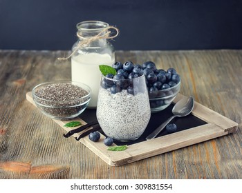Healthy breakfast or morning snack with chia seeds vanilla pudding and berries on wooden rustic background, vegetarian food, diet and health concept