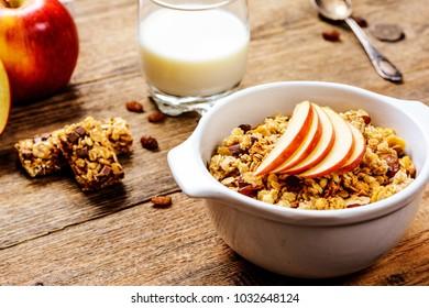Healthy breakfast. Muesli with apple,raisins, muesli bar and milk
