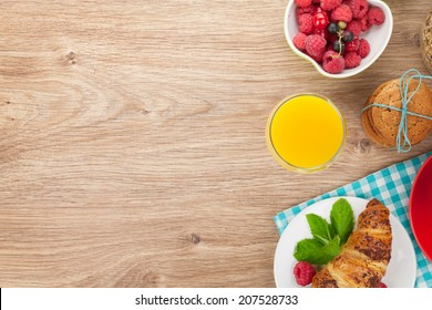 Healthy breakfast with muesli, berries, orange juice, coffee and croissant. View from above on wooden table with copy space