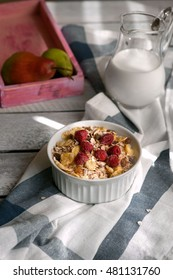 Healthy breakfast. Muesli with berries in white bowl with milk and pears on wooden background.