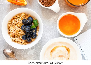 Healthy breakfast - muesli with blueberry and honey, yogurt, croissant, juice and coffee. Selective focus. Top view. Flat lay