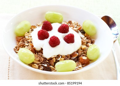 Healthy breakfast with muesli, fresh yoghurt, grapes and raspberries