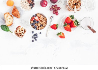 Healthy breakfast with muesli, fruits, berries, nuts on white background. Flat lay, top view.