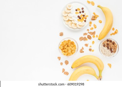 Healthy breakfast with muesli, fruits, fresh banana, cereal, nuts on white background. Flat lay, top view