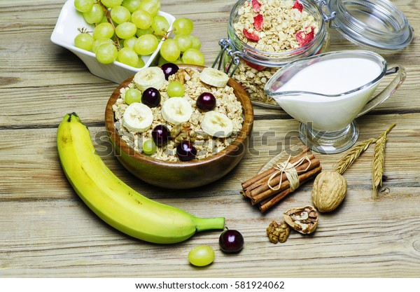 Healthy breakfast with muesli and granola in wooden bowl placed with fresh fruits, cinnamon, nuts and jug of warm milk on wooden background.