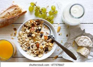 Healthy breakfast with muesli, grapes, cheese and juice on rustic white table from above.
