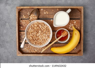 healthy breakfast: muesli, milk and honey on a wooden tray. view from above
