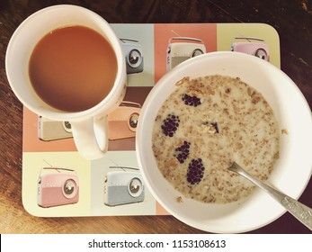 healthy breakfast muesli sultanas with milk in white bowl with spoon and a cup of tea in white mug on plate mat. Muesli breakfast