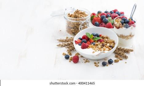 healthy breakfast with natural yogurt, muesli and berries and white background, horizontal
