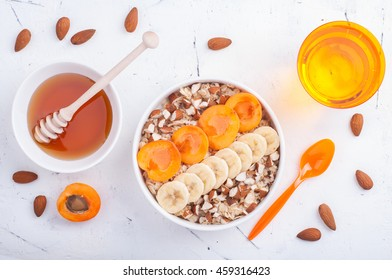 Healthy breakfast. Oatmeal with apricots, bananas, almonds and honey on light background. Flat lay. Top view