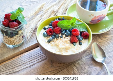 Healthy breakfast - oatmeal with berries and a cup of green tea