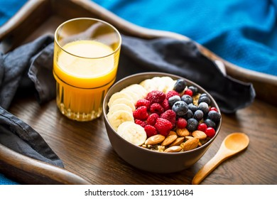 Healthy breakfast with oatmeal bowl, berries , banana and orange juice in wooden tray, bed breakfast