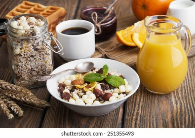 Healthy breakfast of oatmeal, croissants, fresh juice, jam and oranges on a wooden background